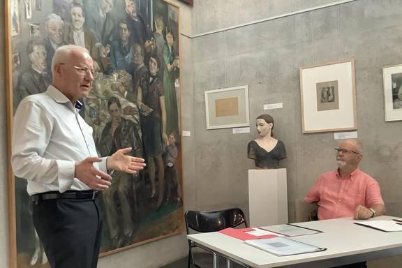 Perter Arlt (links), Kurator der Ausstellung, und Michael Finger (rechts), Vorsitzender des Förderkreises der Willi-Sitte-Galerie, sprechen über das ausgestellte Bild von Harald Metzkes.